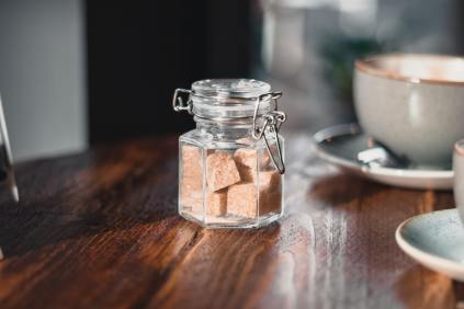 clear-condiment-shaker-with-brown-sugar-cubes-near-gray-986739